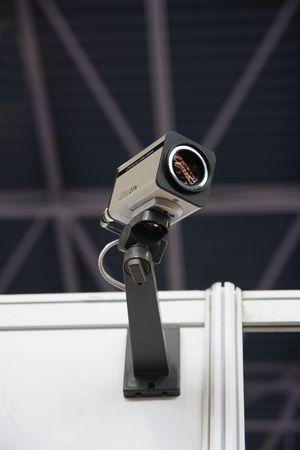 CCTV security camera on dark ceiling background. Stock Photo