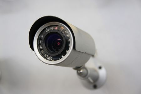 CCTV security camera on white wall background. Standard-Bild