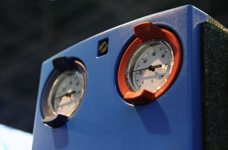 Two thermometers on industrial equipment box.
