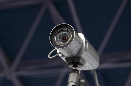CCTV security camera on dark blue background.