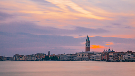 View of the St. Mark's Bell Tower and the city of Venice, Italy under sunset