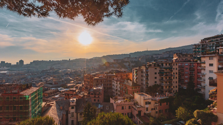View of houses on hills under sunset in Genoa, Italy