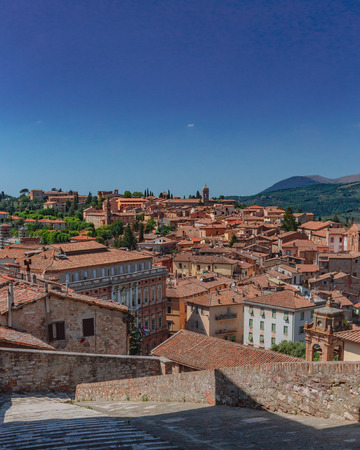 Medieval buildings and houses of Perugia, Italy, under blue sky