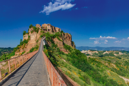 Footbridge leading to Civita di Bagnoregio, the dying city, in Italy, under blue sky