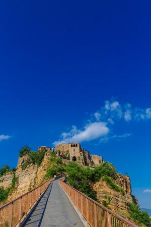 Footbridge leading to Civita di Bagnoregio, the dying city, in Italy, under blue sky