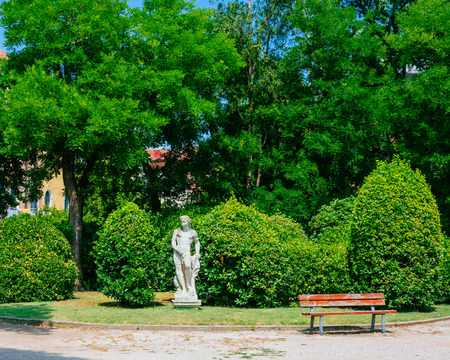 Statue among green trees in the public garden of Venice, Italy