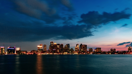 View of skyline of downtown Boston over water at sunset, in Boston, USA