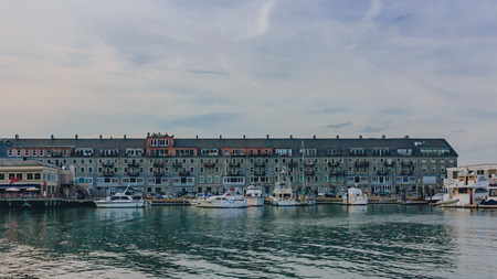 Houses on pier and boats in the harbor near North End of Boston, USA