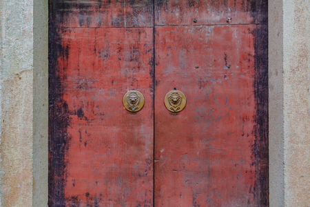 Textured red metal gates, with Chinese lion head door knockers