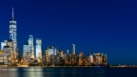 Night view of skyline of downtown Manhattan over Hudson River under dark blue sky, viewed from New Jersey, in New York City, USA Stock Photo