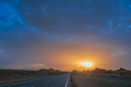 Car traveling on road in the middle of gobi desert at sunset in Dunhuang Yardang National Geopark, Gansu, China 写真素材
