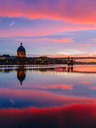 Coucher de soleil rose et bleu sur la Garonne, avec des reflets du pont Saint-Pierre et de la chapelle de l'hôpital Saint-Joseph de la Grave, à Toulouse, France