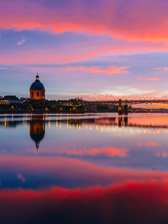 Pink and blue sunset over Garonne River, with reflections of Saint-Pierre Bridge and Chapel of hopital Saint-Joseph de la Grave, in Toulouse, France