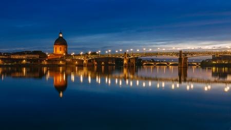 Vue sur la Garonne la nuit, avec des reflets du pont Saint-Pierre et de la chapelle de l'hôpital Saint Joseph de La Grave, à Toulouse, France