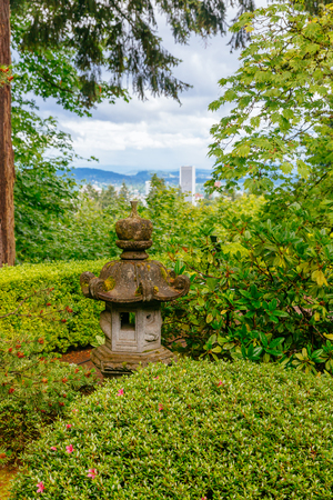 Pagoda-shaped light among trees with view of the city in the distance, at Portland Japanese Garden, Portland, USA