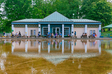 Boston, USA - May 27, 2016: Locals resting at tables by Frog Pond and Frog Pond Pavilion, with their reflections in the water, in Boston Common Editorial