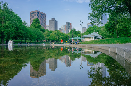 Boston, USA - May 27, 2016: View of Frog Pond in Boston Common with reflection of buildings and locals walkings and resting by the water