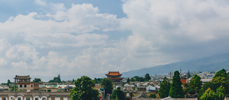 View of houses of old town of Dali under mountains and clouds, in Dali, Yunnan, China