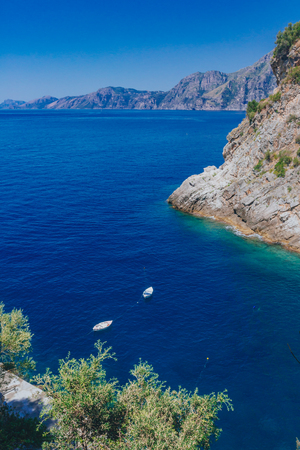 View of boats over blue water and coastline near the town of Praiano, along the Amalfi Coast, Italy