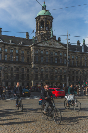 Amsterdam, the Netherlands - March 4, 2017: Locals biking past Royal Palace Amsterdam