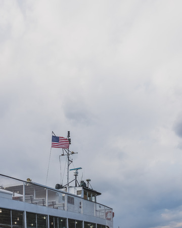 USA national flag flying over cruise boat against  clouds, in New York City, USA