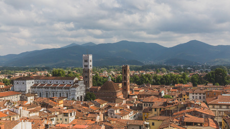 View of St Martin Cathedral and towers over houses, against mountain landscape, in Lucca, Tuscany, Italy Standard-Bild - 122389793