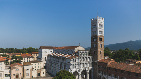 Front facade of St Martin Cathedral and tower viewed from the tower of former church of Saints Giovanni and Reparata, in the historic centre of Lucca, Tuscany, Italy Standard-Bild - 122389836