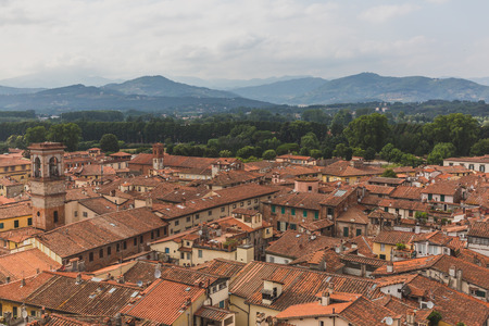 View of architecture and buildings of Lucca, Tuscany, Italy, with mountain landscape in the distance Standard-Bild - 122390057