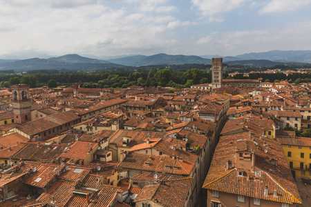 View of architecture and buildings of Lucca, Tuscany, Italy, with mountain landscape in the distance Standard-Bild - 122390140