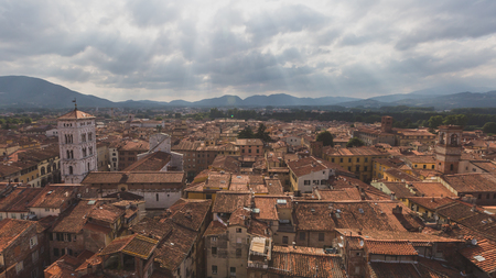 View of architecture and buildings of Lucca, Tuscany, Italy, with mountain landscape in the distance