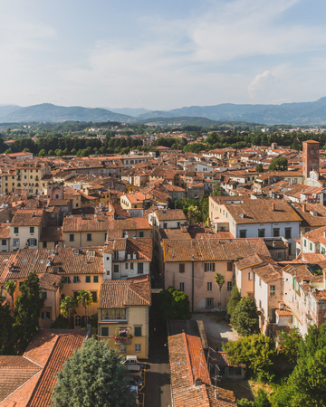 View of architecture and buildings of Lucca, Tuscany, Italy, with mountain landscape in the distance Standard-Bild - 122390280