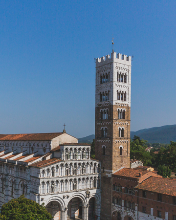 Front facade of St Martin Cathedral and tower viewed from the tower of former church of Saints Giovanni and Reparata, in the historic centre of Lucca, Tuscany, Italy Standard-Bild - 122390318
