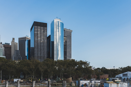 New York City, USA - Oct. 23, 2018: Skyscrapers in lower Manhanttan over trees and contruction site in Battery Park Standard-Bild - 122541743