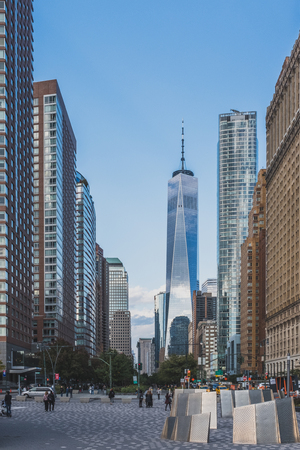 New York City, USA - Oct. 23, 2018: World Trade Center between buildings over busy street, viewed from Battery Park in Lower Manhattan