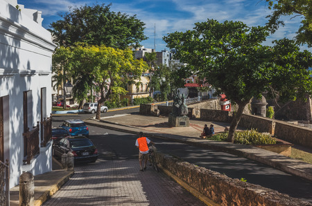 San Juan, Puerto Rico, USA - Jan. 2, 2018: Streets and buildings of Old San Juan with locals walking and sitting by street Standard-Bild - 122739109