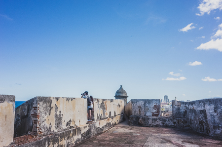 San Juan, Puerto Rico, USA - Jan. 2, 2018: tourists taking photos at San Cristobal fort, with skyline of San Juan in the distance Standard-Bild - 122739110