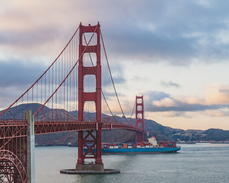 Golden Gate Bridge over San Francisco Bay at dusk, with cargo ship going under the bridge, in San Francisco, USA Standard-Bild - 123158966