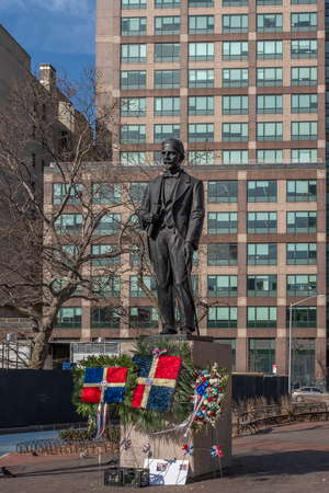 New York City, USA - Feb. 28, 2019: Statue of Juan Pablo Duarte, one of the founding fathers of the Dominican Republic, at Duarte Square, with Dominican flags and flowers Standard-Bild - 123883664