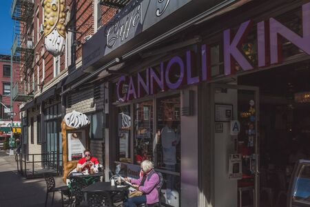 April 10, 2019 - New York City, USA: People in outdoor seating of a cannoli shop in Manhattan Little Italy Editorial