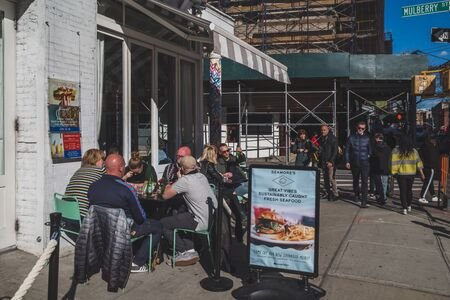 April 10, 2019 - New York City, USA: People eating at outdoor seating of a restaurant in lower Manhattan