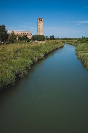 Cathedral of Santa Maria Assunta and bell tower by river on island of Torcello, in Venice, Italy