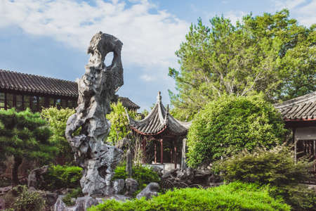 Giant rock in garden by Chinese architecture at Lingering Garden Scenic Area in Suzhou, Jiangsu, China Stock Photo