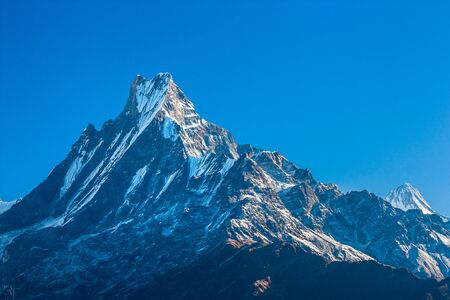 Top of the mountain peak summit in clear blue sky. Himalayas
