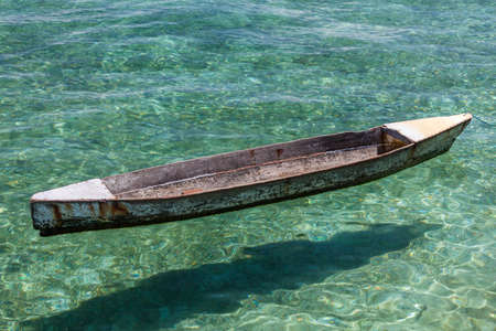 Traditional wooden boat in crystal clear lagoon