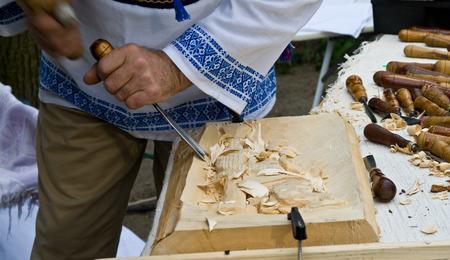 trinchante: Hombre rumano tallador de trabajo en la escultura de madera Foto de archivo