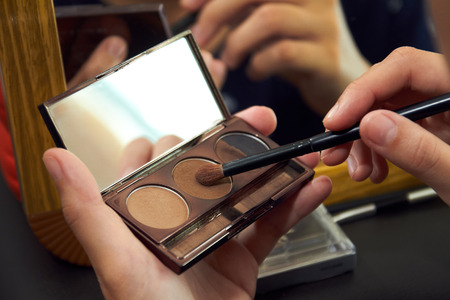 Makeup artist applying colorful eyeshadow on model's eye with a eyeshadow palettes Eye shadow is a cosmetic that is applied on the eyelids and under the eyebrows.