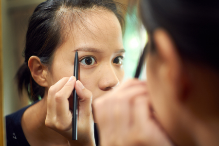 Žena asijské dívka drží štětec na obočí vyplnit obočí