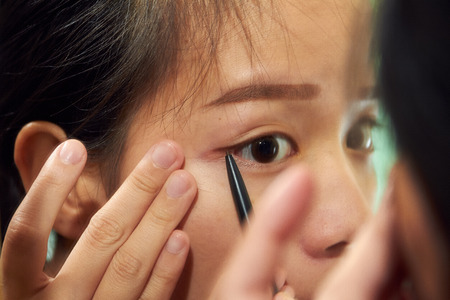 fake eyelashes: Woman asian girl holding a brush at her eyebrows fill in eyebrow
