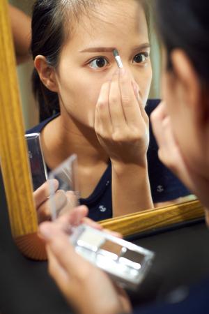 Žena asijské dívka drží štětcem na obočí vyplní obočí