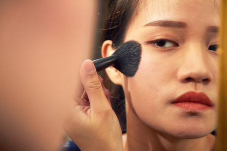 Beautiful young girl puts powder on the face by means of a brush for a make-up - indoors. Blusher & Cheek Makeup Including Cheek Stain 스톡 콘텐츠